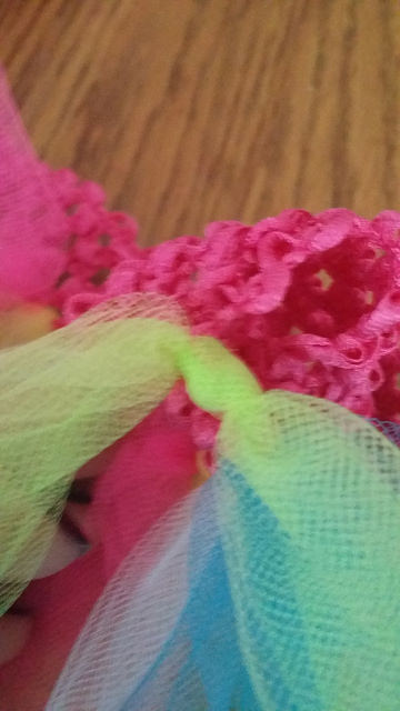 Pull it tight, taking care not to catch the neighboring tulle or crochet band